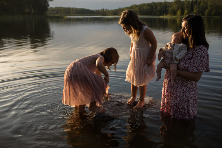 mom and her daughters wade in water during event by Edmonton family photographers