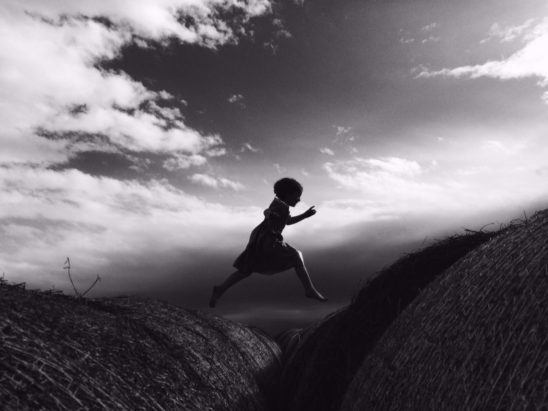 black and white iphone photo of child jumping between round bales on family farm