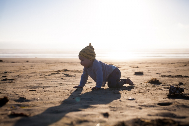 baby crawling across beach for unscripted child portrait