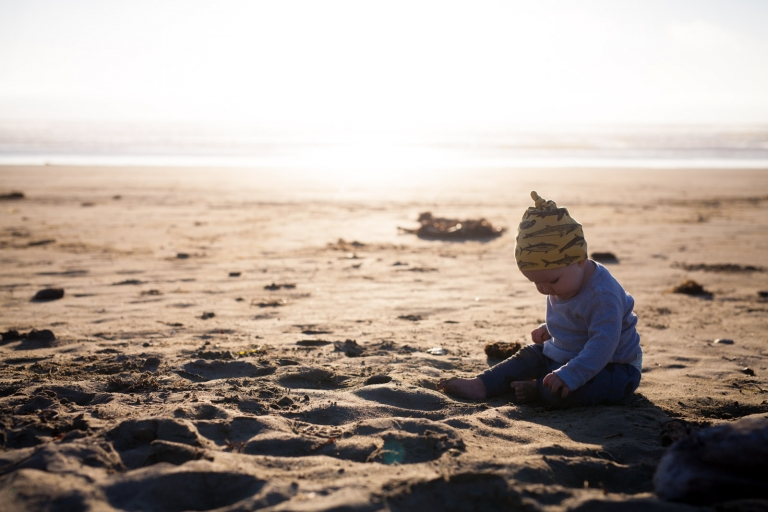 baby sitting alone in sand on beach