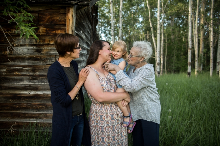 mom holds her toddler surrounded by her mother and grandmother in Parkland County, Alberta