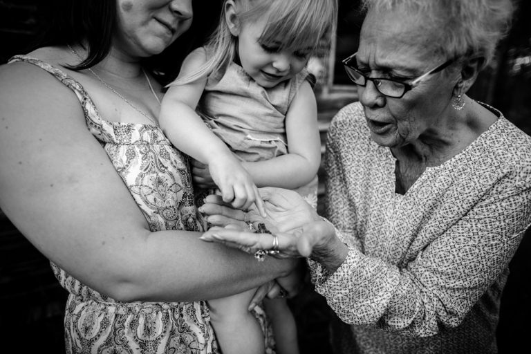 great grandmother holds tiny frog for her great granddaughter to see