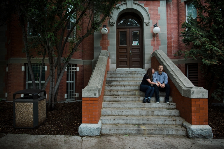 engaged couple cuddles together on steps of historic Edmonton building