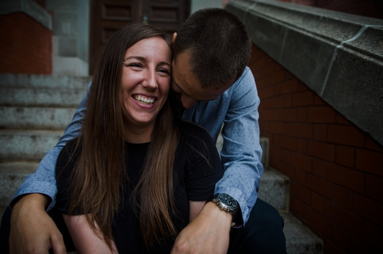man snuggles into his fiancee's neck during their summer engagement session before their wedding