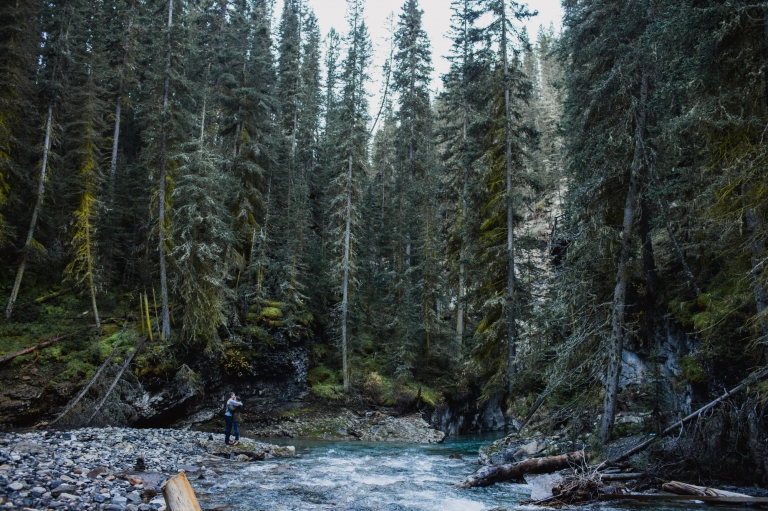 wide angle photo of couple hugging next to creek in Johnston Canyon