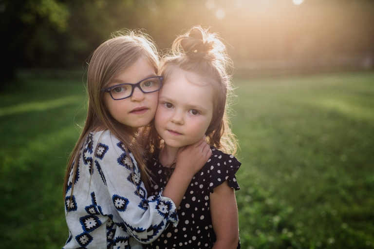 two sisters pose in golden hour light during Hobbs Photography's unique back to school portrait sessions