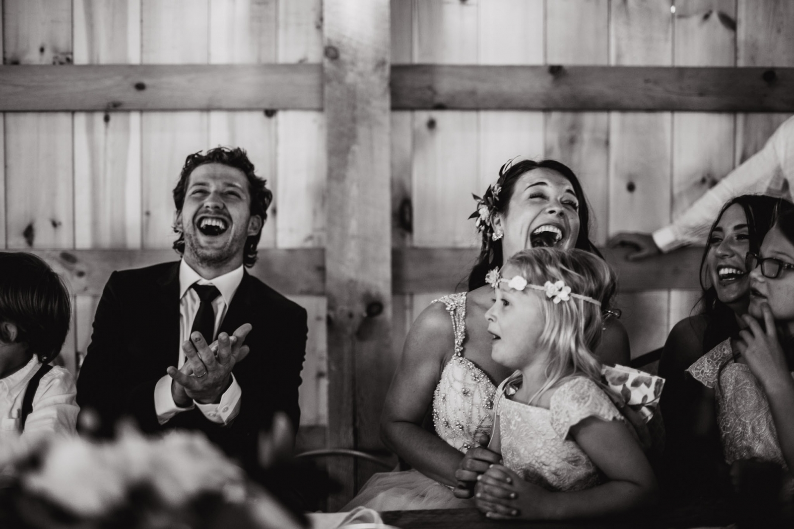 newlyweds laugh during wedding speeches in Lions Garden rustic wedding venue