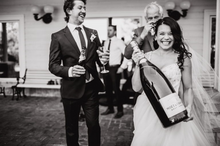 a bride's smile is as big as her bottle of champagne to celebrate her outdoor wedding in Parkland County