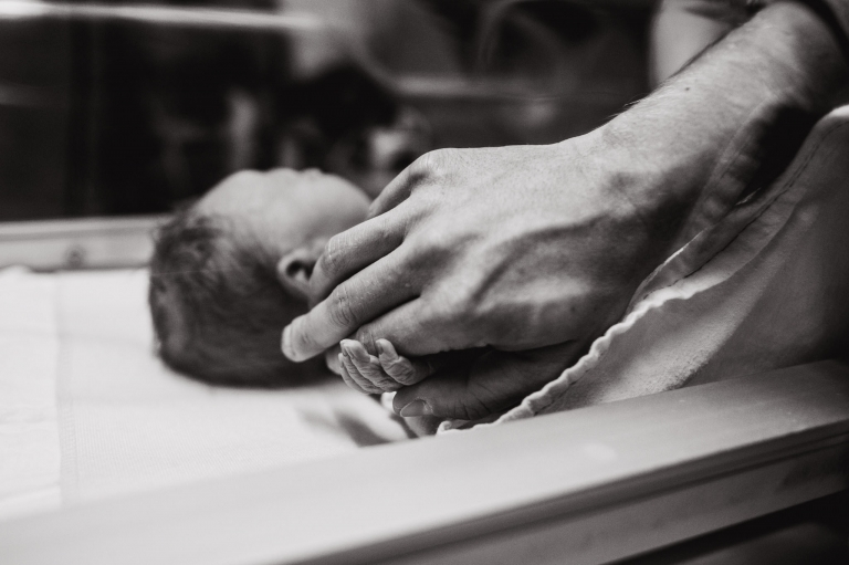 a newborn hold's his dad's finger
