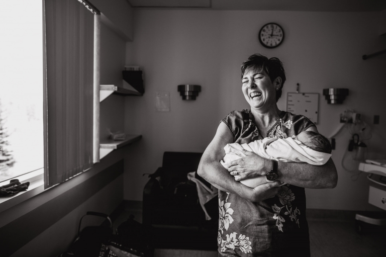 a new grandmother laughs with joy as she holds her new granddaughter