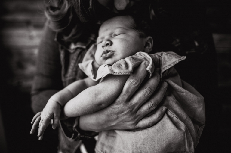 a beautiful newborn held by her mom during a lifestyle studio newborn session