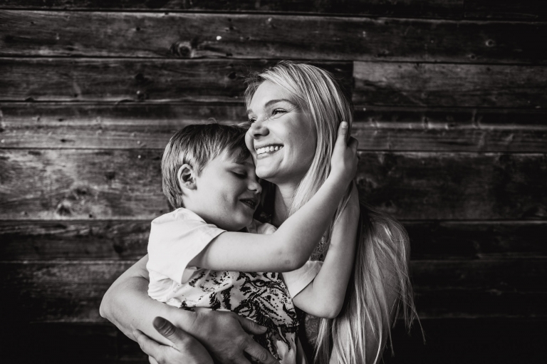 A boy cuddles him mom against the barn board wall in our studio just west of Edmonton