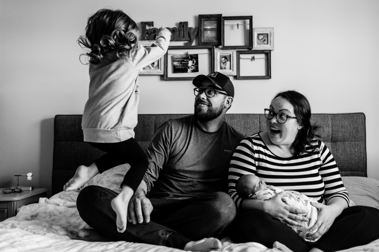 big sister bounces on the bed with mom, dad and baby brother during a lifestyle newborn session in their home