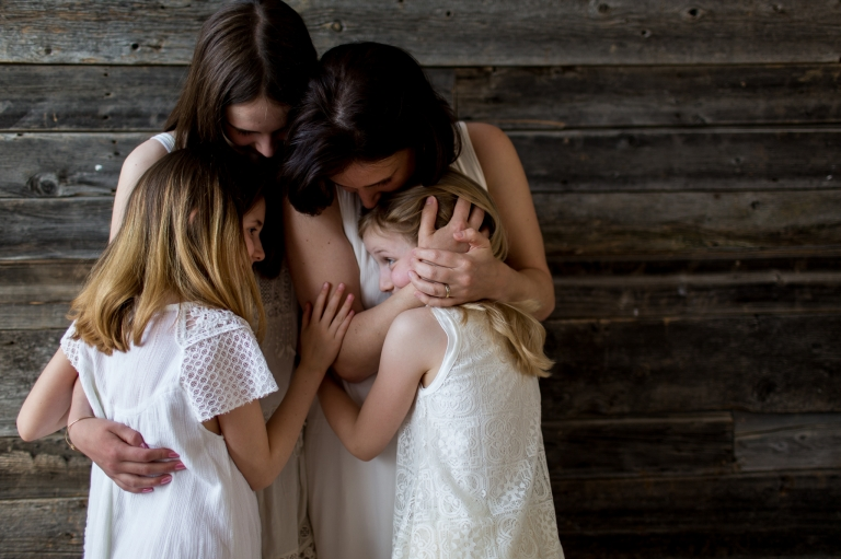 a loving mother and her three daughters hold each other close in The Grain Shed Studio