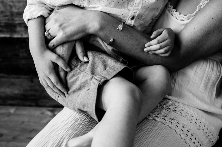 a detail shot of a mother and her son's hands as he snuggles on her knee