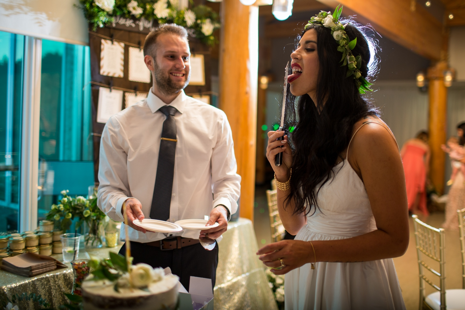 a groom smiles as his wife licks the knife after cake cutting in a fun wedding photo