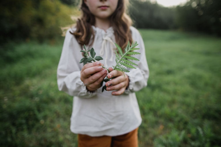 child holds greenery in her hands playing outside