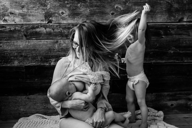 mom breastfeeds baby while toddler plays with her hair in simple studio session