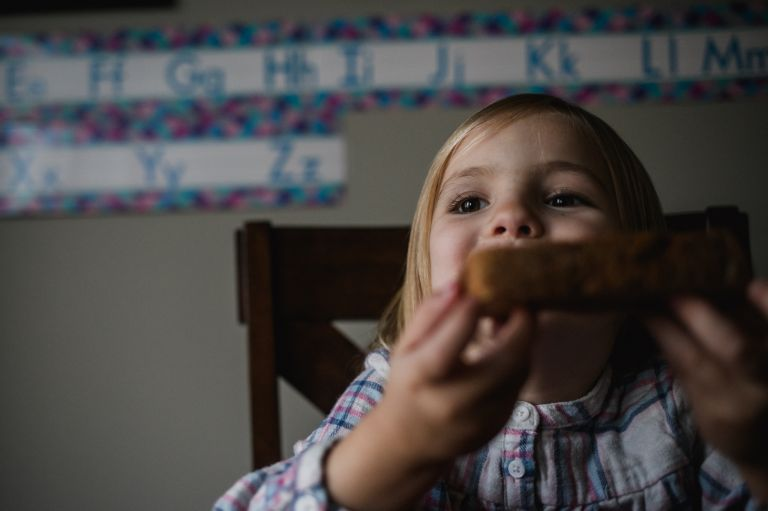 little girl eats toast at home