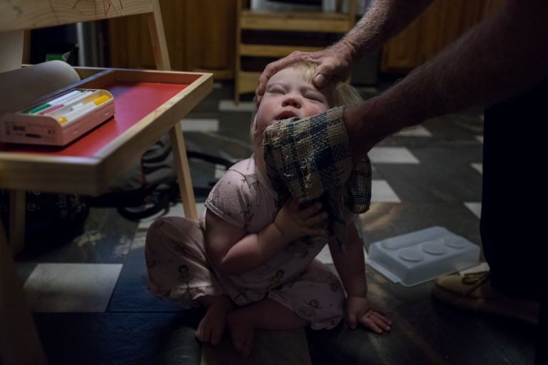 a dad wipes his toddler daughter's face