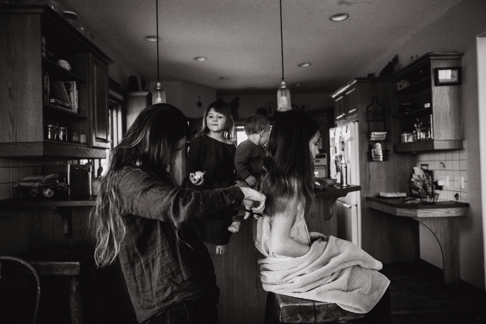 mom trims her daughter's hair in the kitchen