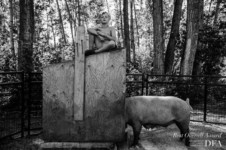 timeless portrait of a child sitting on a pig feeder