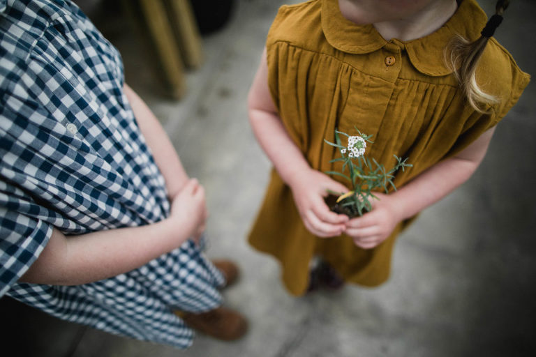 child in mustard dress holds small plant