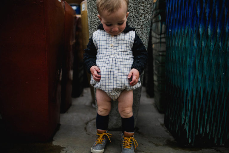toddler stands in outfit purchased from a small local shop