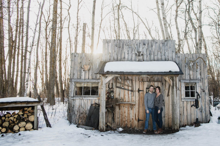couple poses in front of rustic building in gorgeous light
