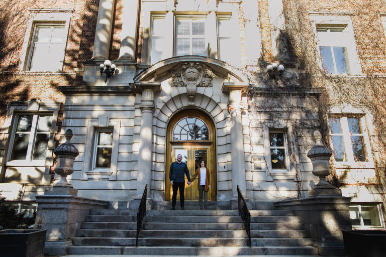 engaged couple stands on steps at U of A