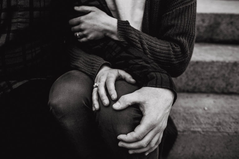 A black and white details shot of a fiance and fiancee's hands