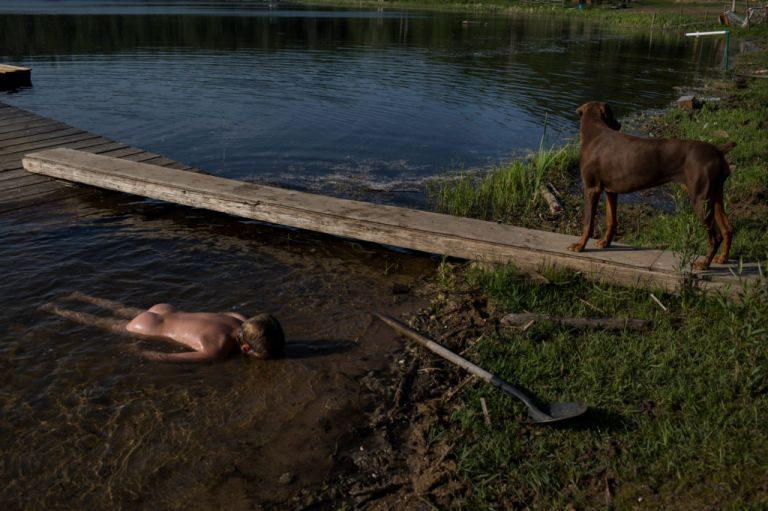 Aimee Hobbs photograph of child laying facedown in shallow water near shovel and dog in information about virtual photography workshop