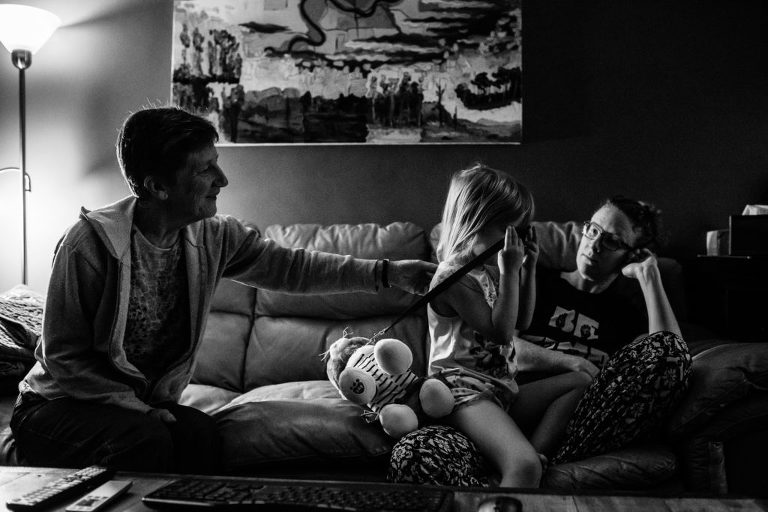 grandma rubs her granddaughters back during a day in the life photography session