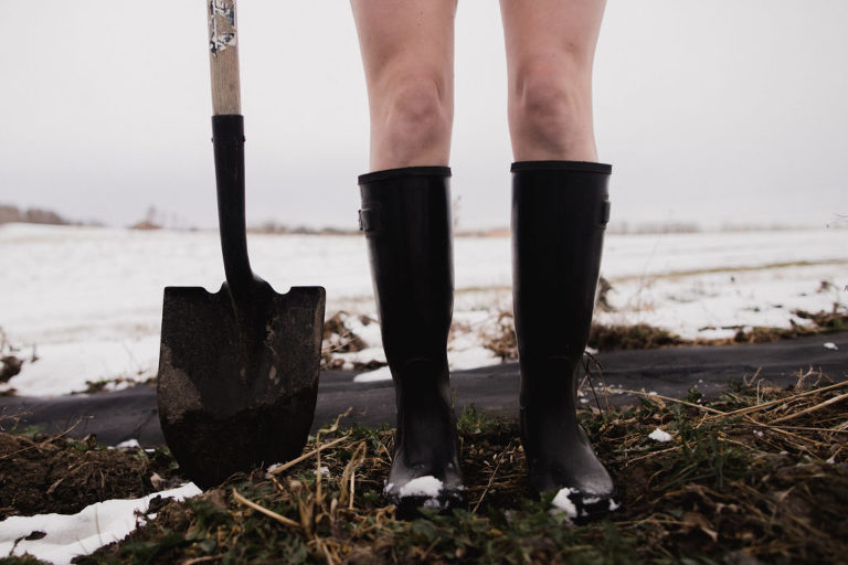 Jenna Hobbs stands in her rubber boots with shovel for World Naked Gardening Day