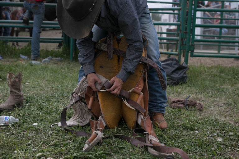 cowboy gets saddle ready for rodeo