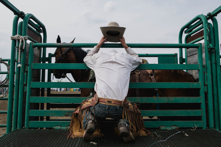 a cowboy prays before riding in rodeo by Jenna Hobbs