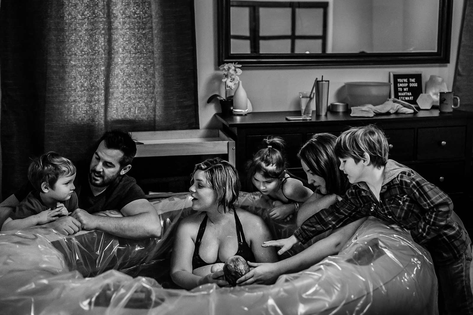 edmonton birth photographer captures entire family welcoming their newborn daughter at their edmonton home waterbirth supported by Hope midwfery