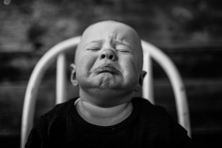 Photographer Aimee Hobbs makes black and white studio portrait of baby pouting on chair