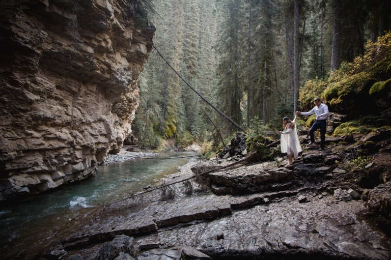 an adventurous couple hold hands in the forest near Banff