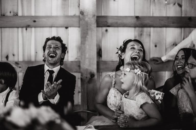 newlyweds laugh during wedding speeches in Lions Garden rustic wedding venue
